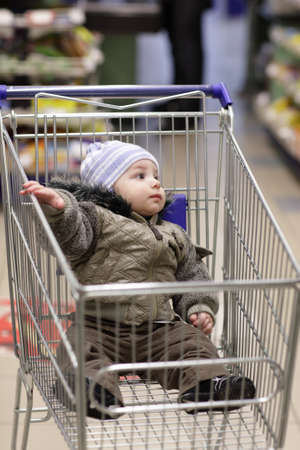 The child in a shopping cart at market photo