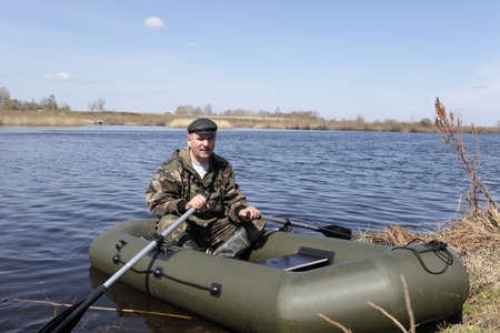 Man is posing on an inflatable boat in summer photo