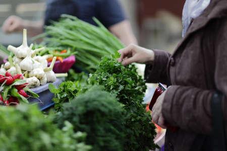 agricultor: La mujer elige a los verdes en un mercado Foto de archivo