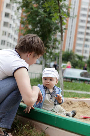 Mother and her toddler are in sandbox in summer Stock Photo - 14189665