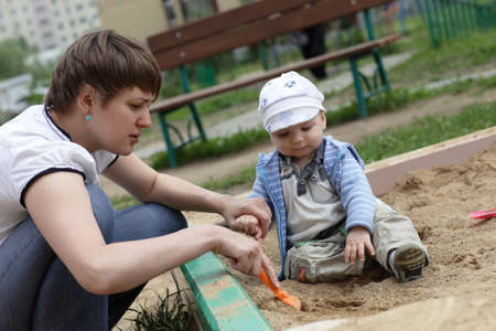the sandbox: Mother playing with her toddler in sandbox