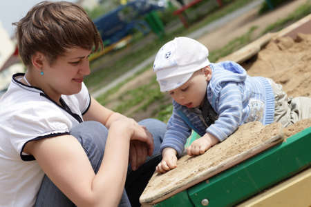 Mother with her toddler ate playing in sandbox in summer Stock Photo - 14189717