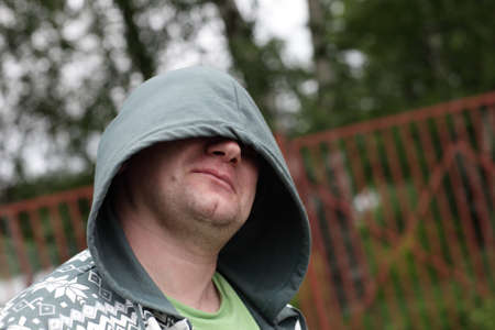 Portrait of man with hood in a park photo