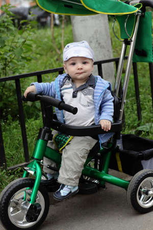 Funny child is on tricycle in a summer park photo