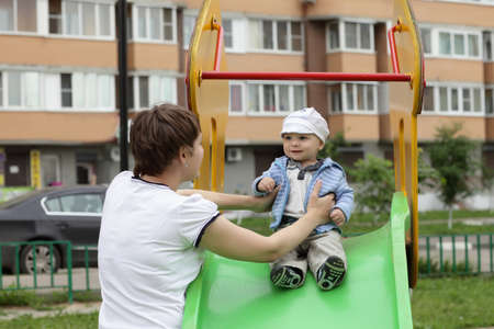 Mother holding her child on a slide at playground Stock Photo - 14265821
