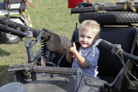 Portrait of child in sidecar with gun photo