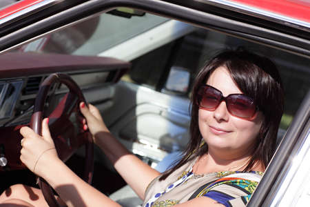 The smiling woman is posing in a car photo