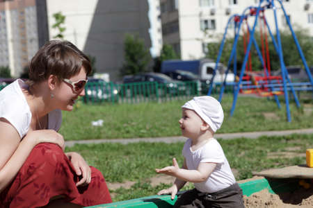 Mother with child are playing in sandbox