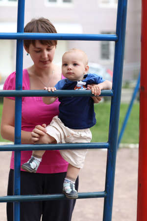 Baby is climbing step ladder with mother photo