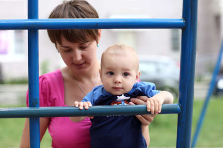 Portrait of baby with his mother on ladder at playground photo