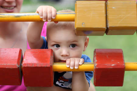Little child is hiding behind wooden blocks at playground photo