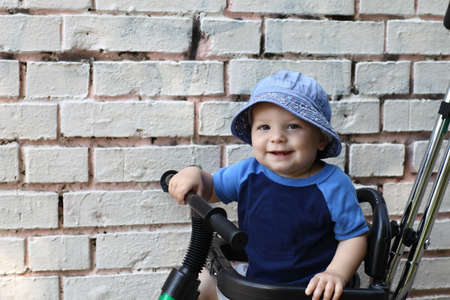 Happy child on bicycle on the brick wall background photo