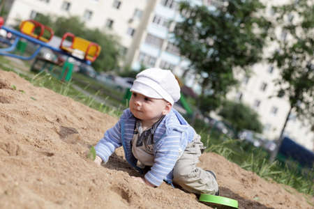 Child is creeping in sandbox at playground Stock Photo - 14634240