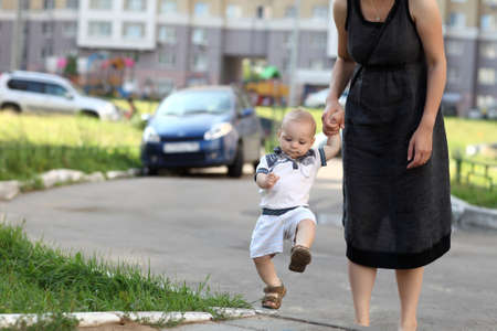 Child climbing on sidewalk with mother photo