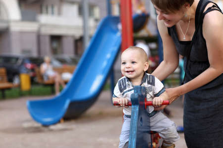 Child is swinging on spring toy horse at playground Stockfoto
