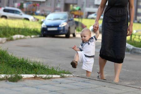 Toddler climbing on sidewalk with mother Standard-Bild