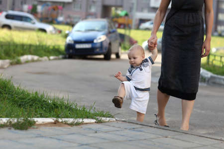 Toddler climbing on sidewalk with mother Stock Photo
