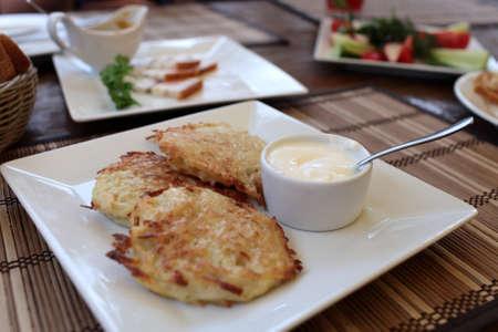 Ukrainian pancakes with sour cream on the white plate photo