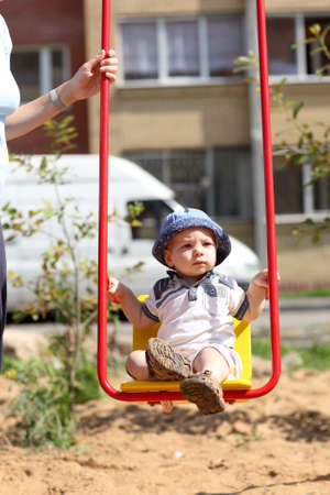 Baby boy is swinging on a swing at playground photo