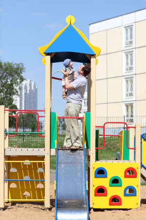 Father with her son are posing on a slide at the playground photo