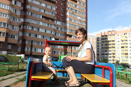 Mother and her son are sitting in toy car at outdoor playground photo