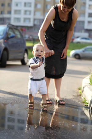 Mother with her baby are walking through puddles photo