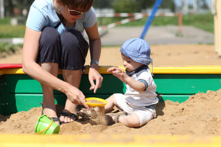 bolter: Mother and her son sifted sand in a sandbox Stock Photo