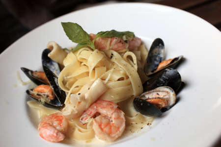 mediterranean cuisine: Pasta with seafood on a plate in an italian restaurant Stock Photo