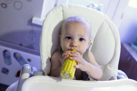 Baby with corn in a high chair photo