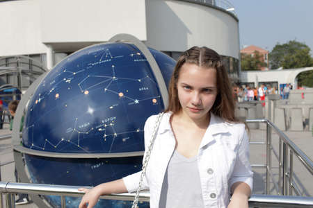 Serious teen is posing on the celestial globe background photo
