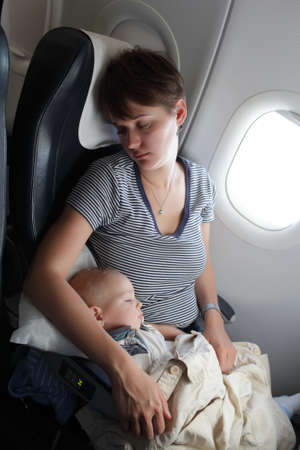 Mother with her baby are sleeping at airplane photo