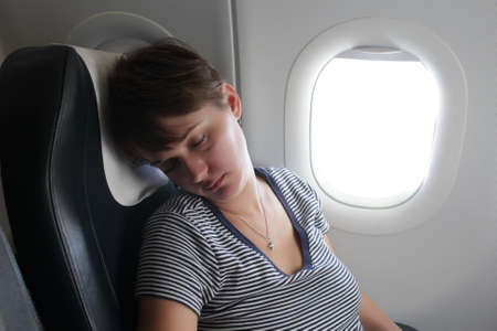 The woman is sleeping at the airplane