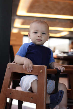 Toddler is sitting in highchair in a restaurant photo