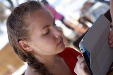 Teenager is using tablet PC in a cafe photo