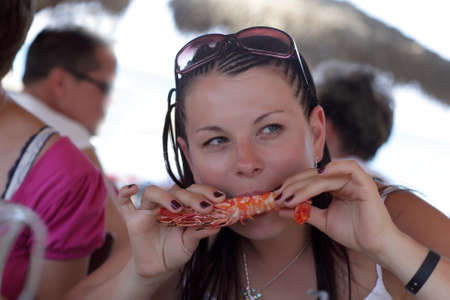 Woman is eating shrimp in a seafood restaurant Stock Photo - 15641029