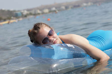 Girl is resting on an inflatable mattress in the sea, Rhodes, Greece