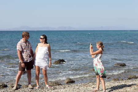 Girl takes picture her parents on the beach, Rhodes, Greece photo