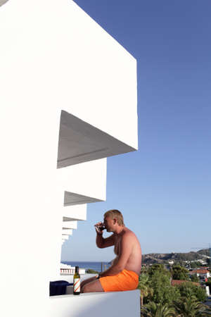 Man is drinking red wine on a white balcony, Greece photo
