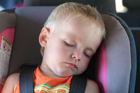 Boy is sleeping in a child car seat Stockfoto
