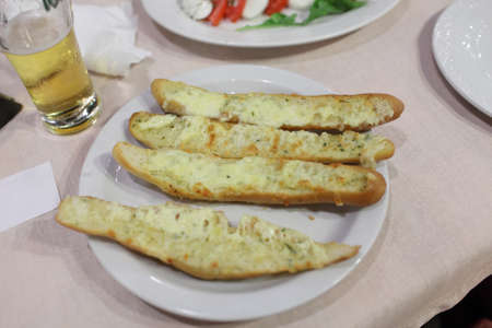Grilled bread with cheese and garlic on a plate in taverna photo