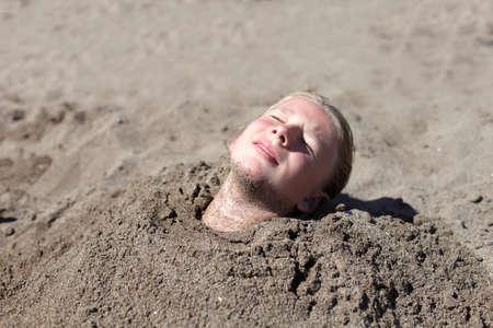 bury: Girl buried in the sand on a beach