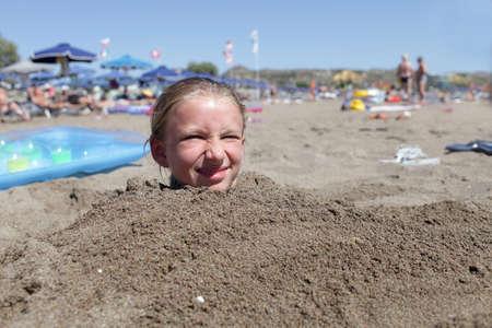 bury: Head of girl on a beach, Rhodes, Greece Stock Photo