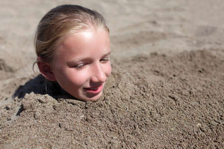 buried: Kid buried in a sand on the beach Stock Photo