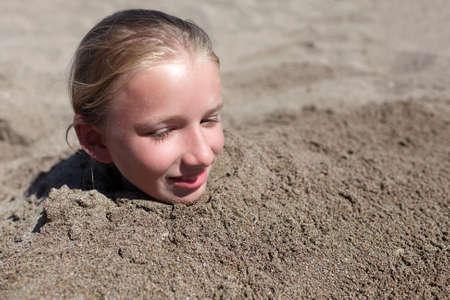 bury: Kid buried in a sand on the beach Stock Photo