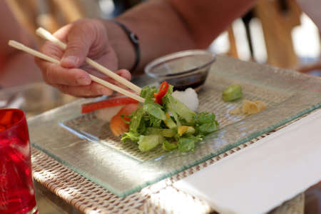 Man is holding lettuce by chopsticks in a japanese restaurant photo