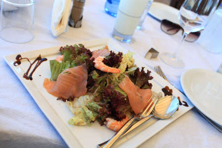 Salad with shrimps and slices of salmon on a white plate Stock Photo - 16297860