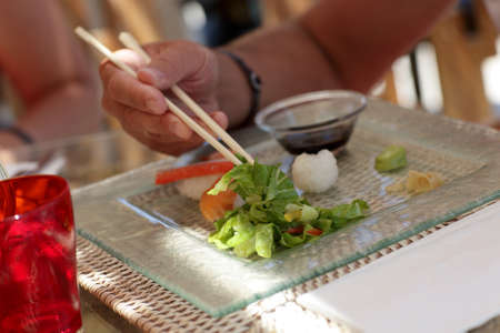 Man is taking lettuce by chopsticks in a japanese restaurant photo