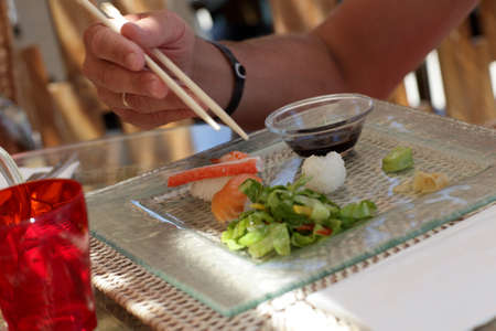 Man is holding chopsticks in a japanese restaurant photo