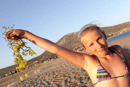 Girl is posing with bunch of grapes on a Prasonisi beach, Rhodes, Greece photo