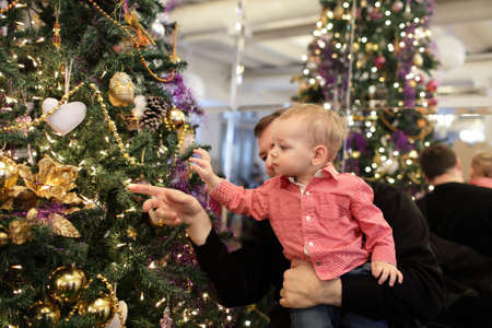 baby near christmas tree: Father with his baby near Christmas tree at home Stock Photo